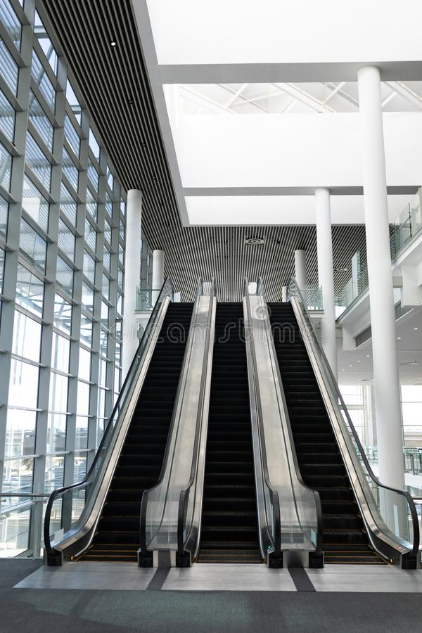 Front view of three modern escalators in a office lobby. Against inside buildings in background royalty free stock images