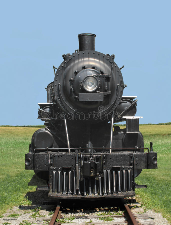 Front View Of A Vintage Black Railroad Train Steam Locomotive On Tracks In Field With Clear Blue Sky The Background