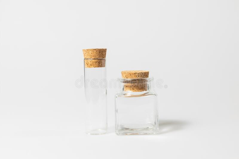 Front view of transparent empty glass jar or test tube bottles with closed brown cork cap lids on white background royalty free stock image