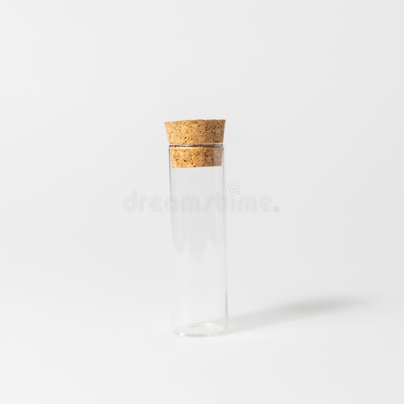 Front view of transparent empty glass jar or test tube bottle with closed brown cork cap lids on white background stock photos