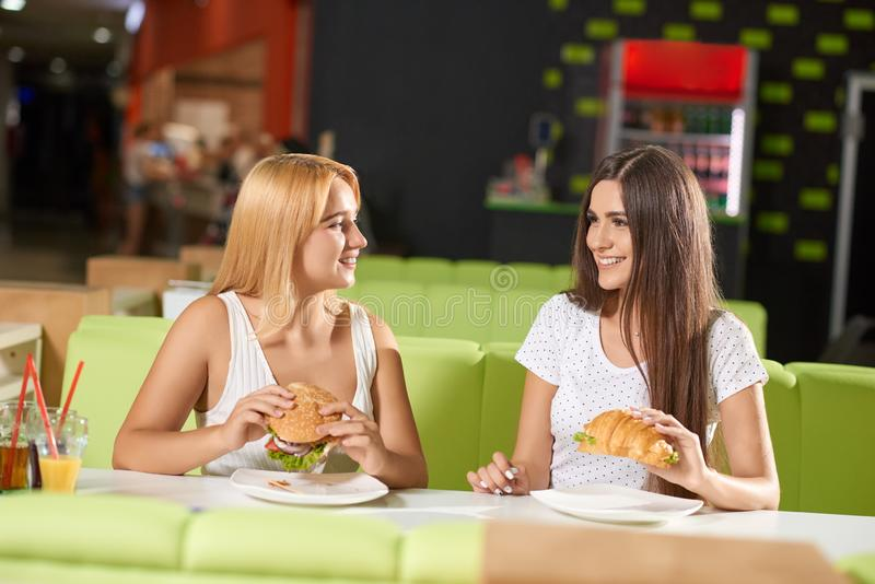 Front view of two girls eating burger and croissant in cafe. Front view of two attractive girls eating delicious burger and croissant in cafe. Brunette and royalty free stock photography