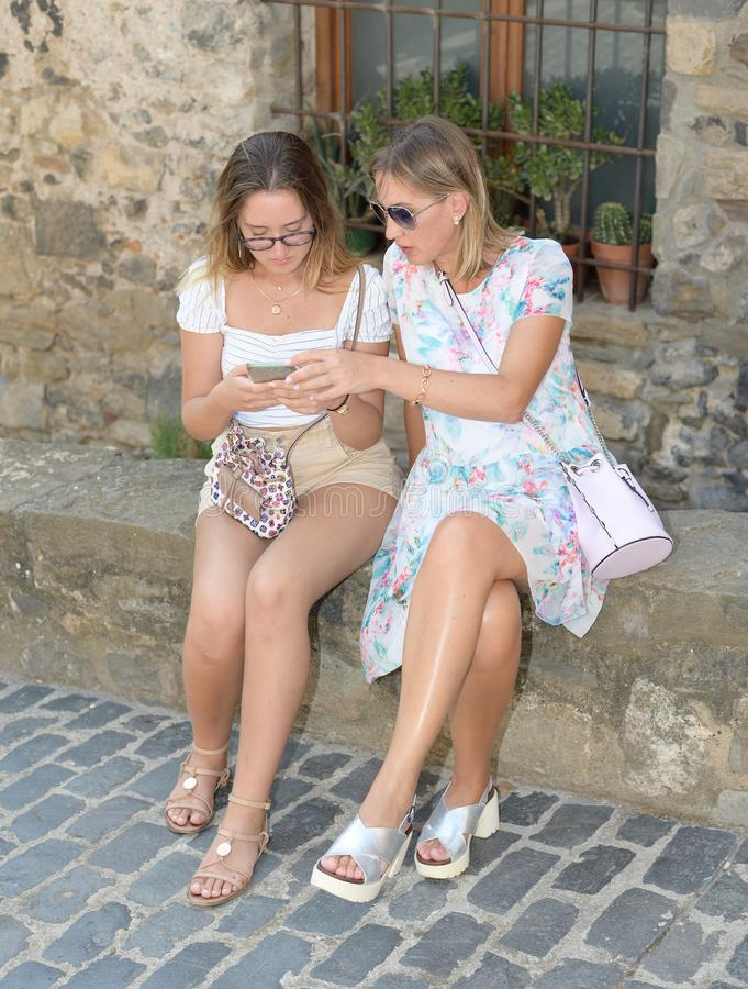 Front view of two women sitting and finding on line content on their smart phones on a street of a medieval village stock photo