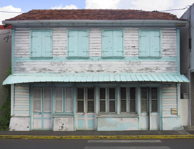 Front view of a typical wooden and rusted house in Martinique, French West Indies. Tropical blue and white windows. Typical wooden and rusted house in Martinique stock photography