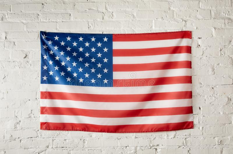 Front view of united states of america flag on white brick wall stock photography