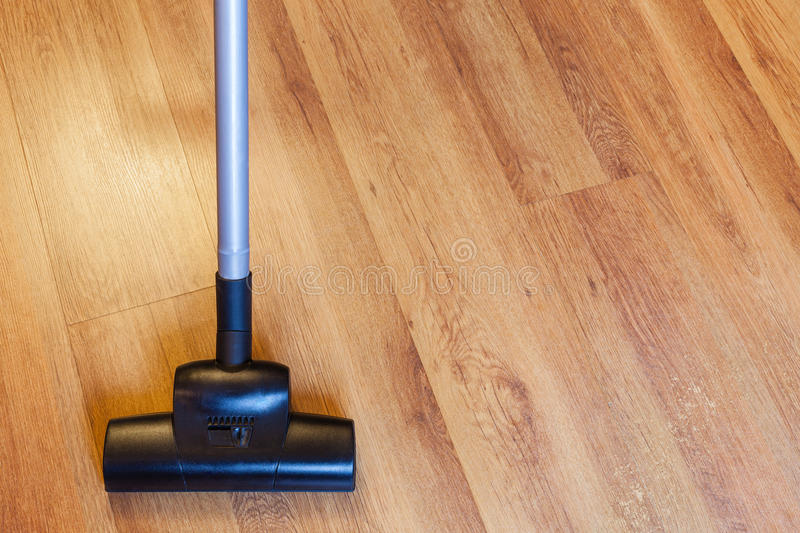 Front view vacuuming of laminate by vacuum cleaner royalty free stock photo