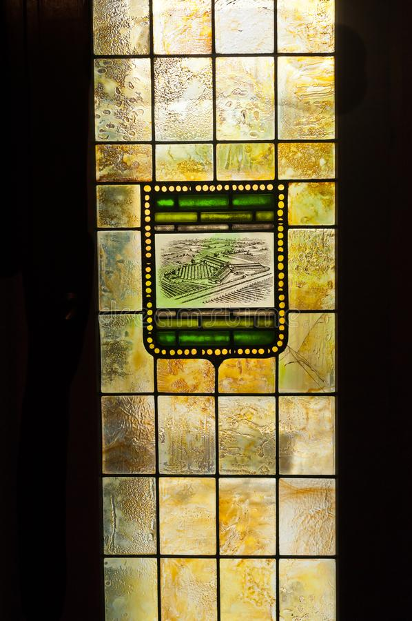 Stained glass windowed door of a wine tasting room in Spain. Front view of a vintage, artisan created, stained glass door, back light by the sun in a vineyard in stock photography
