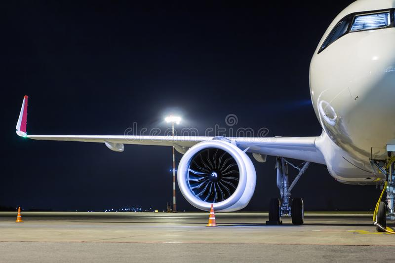 Front view of a white passenger airplane connected to an external power supply on an airport night apron royalty free stock image