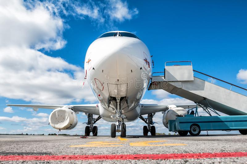 Front view of white passenger airplane with boarding ramp at the airport apron stock photo