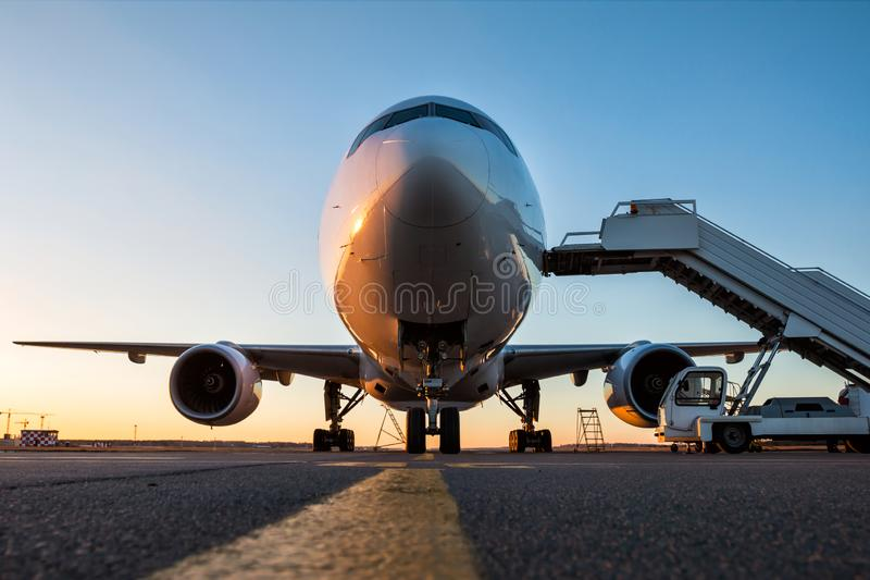 Front view of white wide body passenger airplane with a boarding stairs at the airport apron in the evening sun royalty free stock photos