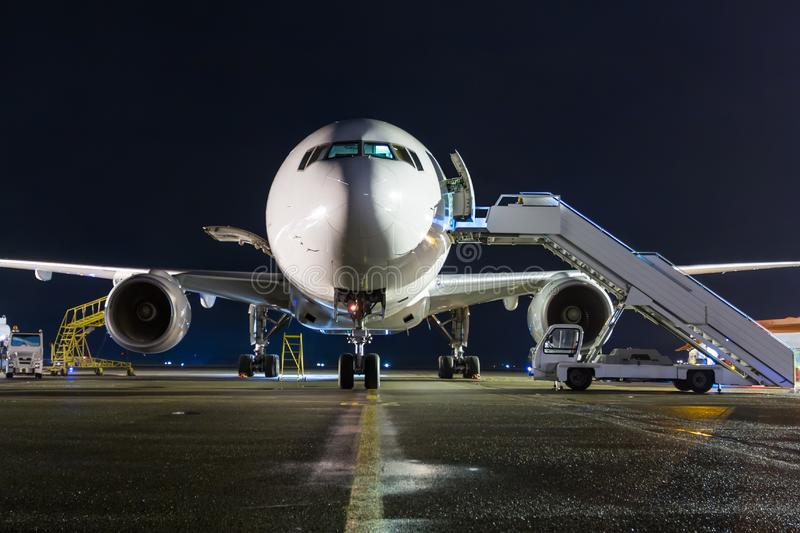 Front view of white wide-body passenger airplane with a boarding steps at the night airport apron stock images