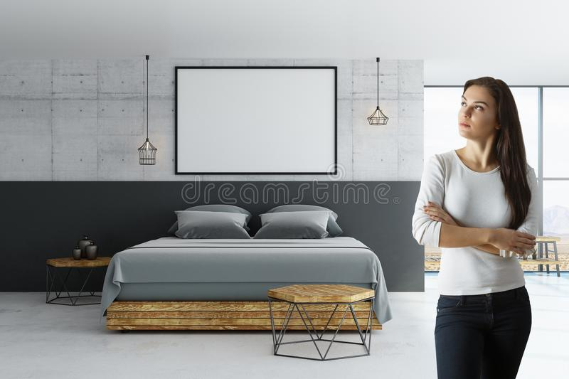 Woman in loft room with blank poster. Front view on woman with blank white poster with black picture frame on concrete wall above wooden bed with grey blanket in stock image