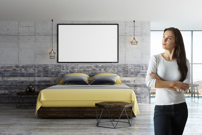 Woman in loft room with blank poster. Front view on woman with blank white poster with black picture frame on concrete wall above wooden bed in loft bedroom stock photo