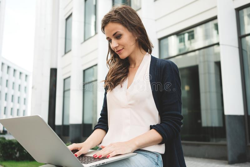 Front view of woman student is work on laptop keyboard on outdoors in urban. Close-up female freelancer is typing text on mobile computer stock images
