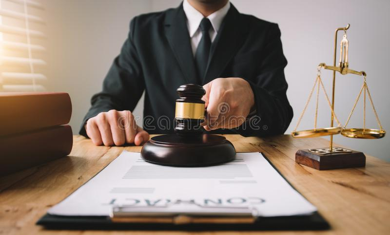 Front view workspace with computer,. Justice and law concept.Male judge in a courtroom on wooden table and Counselor or Male lawyer working in office. Legal law royalty free stock photo