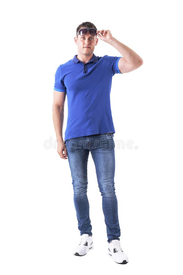 Front view of young adult casual man remove sunglasses and looking at distance. Full body isolated on white background royalty free stock image