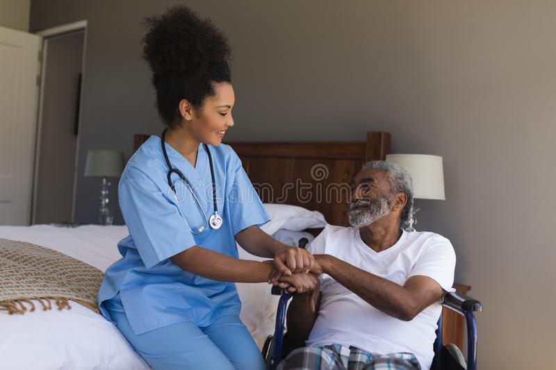 Female doctor consoling senior man in bedroom royalty free stock image