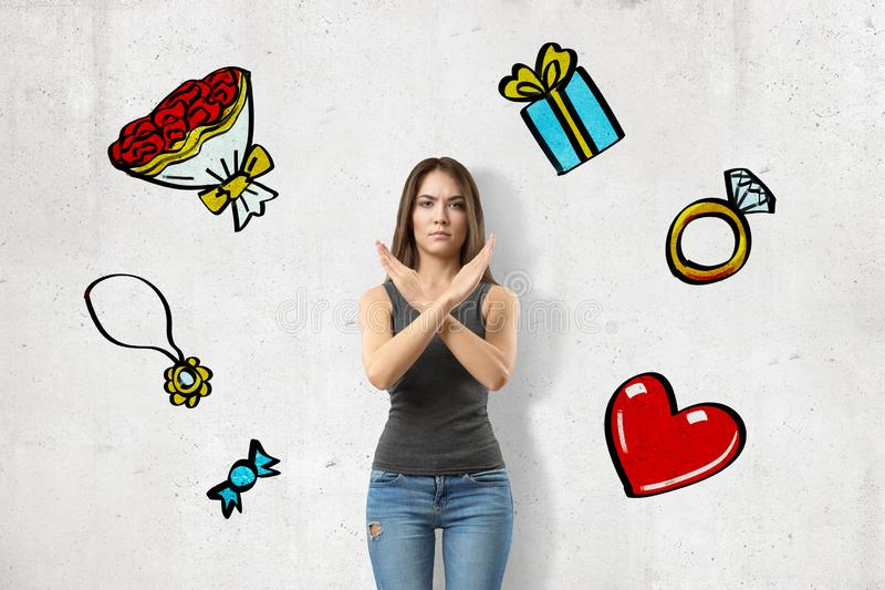 Front view of young angry girl, crossing arms in stop gesture, standing at wall with images of ring, gift, bouquet royalty free stock image