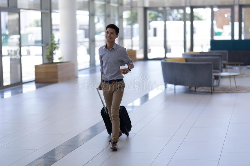 Asian male executive walking with luggage in the lobby stock photo