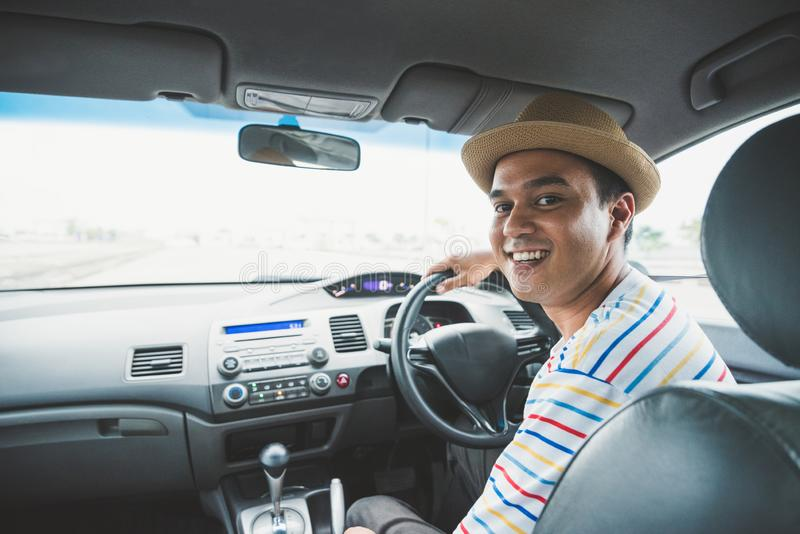 Front view of young asian man driving car. stock photo
