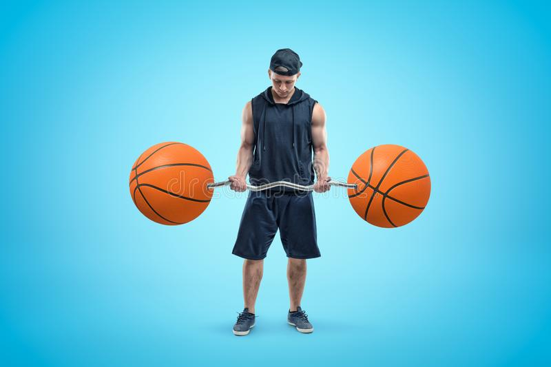 Front view of young athlete in black cap, sleeveless hoodie and shorts, standing and looking down at barbell in his stock photo