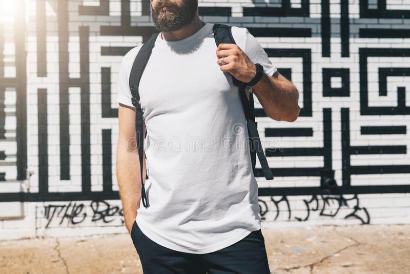 Front view. Young bearded millennial man dressed in white t-shirt is stands against brick wall. Mock up. Summer day. Front view. Young bearded millennial man royalty free stock image