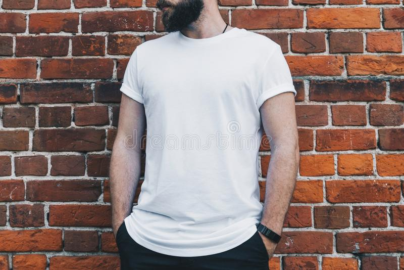 Front view. Young bearded millennial man dressed in white t-shirt is stands against dark brick wall. Mock up. stock images
