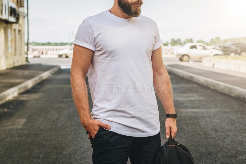 Front view. Young bearded millennial man dressed in white t-shirt is stands on city street. Mock up. stock photos