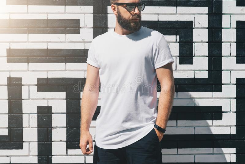 Front view. Young bearded millennial man dressed in white t-shirt and sunglasses is stands against brick wall. Mock up. Summer day. Front view. Young bearded stock photo