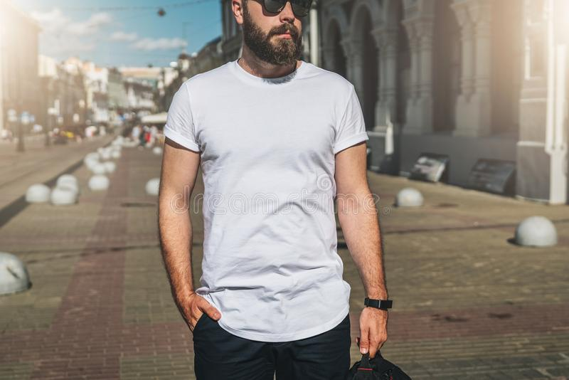 Front view. Young bearded millennial man dressed in white t-shirt and sunglasses is stands on city street. Mock up. royalty free stock photos