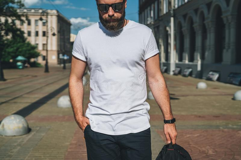 Front view. Young bearded millennial man dressed in white t-shirt and sunglasses is stands on city street. Mock up. royalty free stock photography