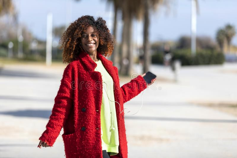 Front view of young beautiful curly african american woman dancing and listening music while looking away outdoors stock photos