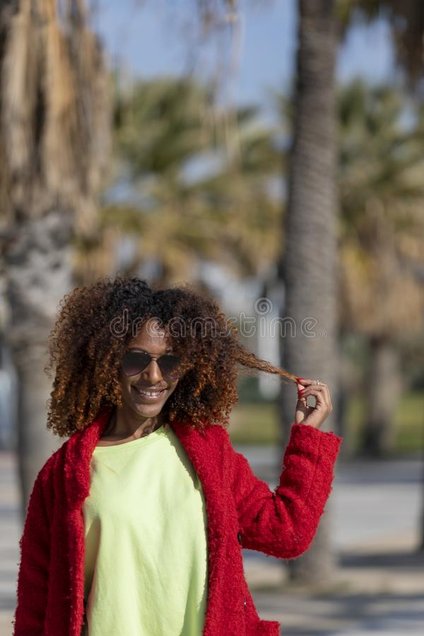 Front view of a young beautiful curly afro woman wearing sunglasses and red jacket standing in a city street while touching hair stock image