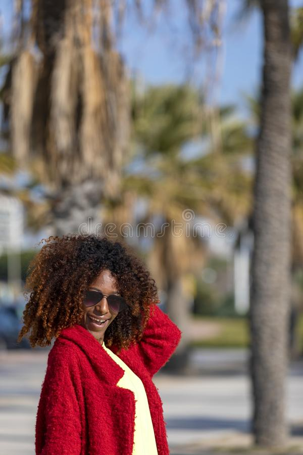 Front view of a young beautiful curly afro woman wearing sunglasses and red jacket standing in a city street while touching hair royalty free stock photography