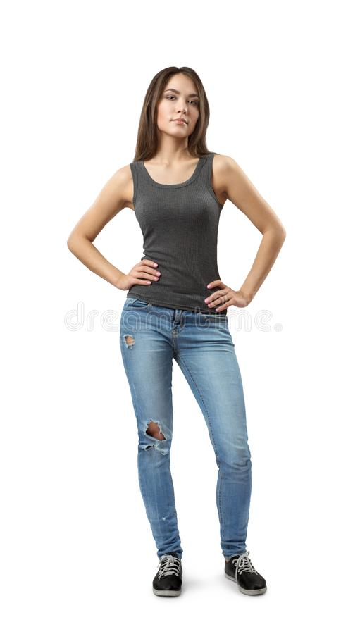 Front view of young beautiful woman in gray sleeveless top and blue jeans standing looking at camera with hands on hips royalty free stock images