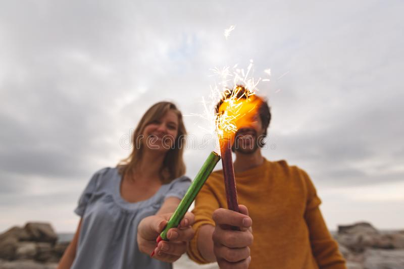 Caucasian couple playing with fire cracker while standing at beach stock photography