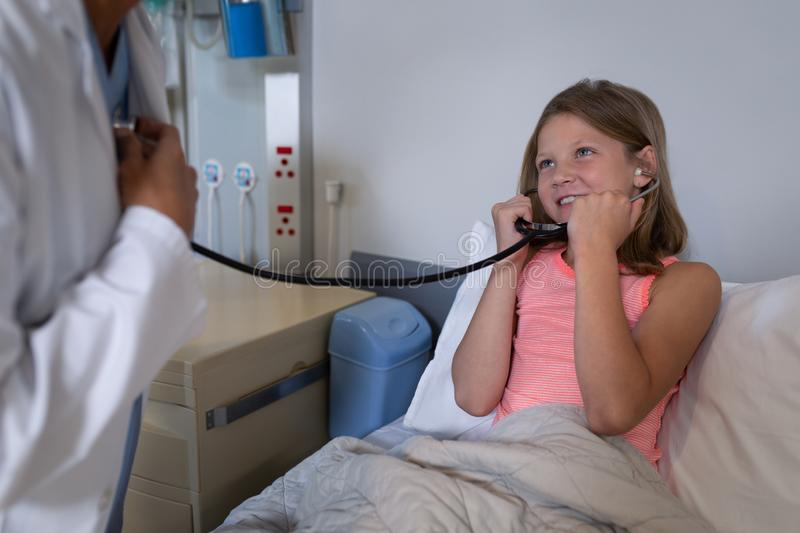 Girl patient listening to doctors heart beat with stethoscope stock photo
