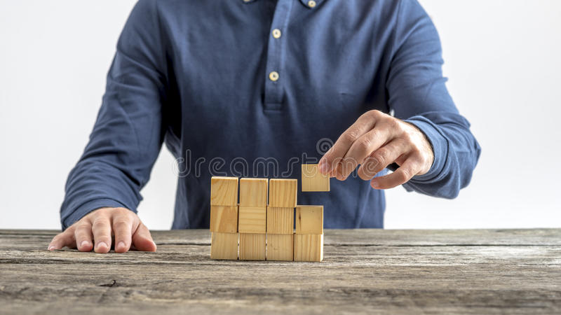 Front view of young creative innovator building a structure with. Wooden cubes. Conceptual of innovation, idea and business start up royalty free stock photography