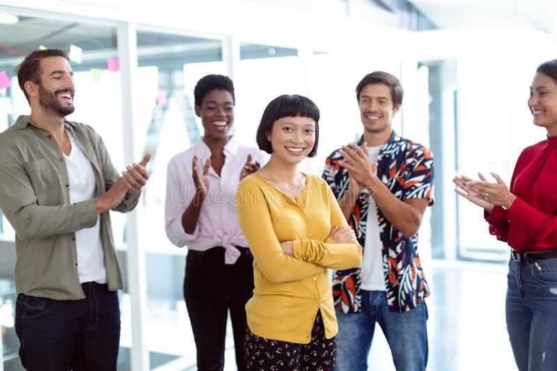 Business people applauding in a modern office. Front view of young diverse business people applauding in a modern office royalty free stock image