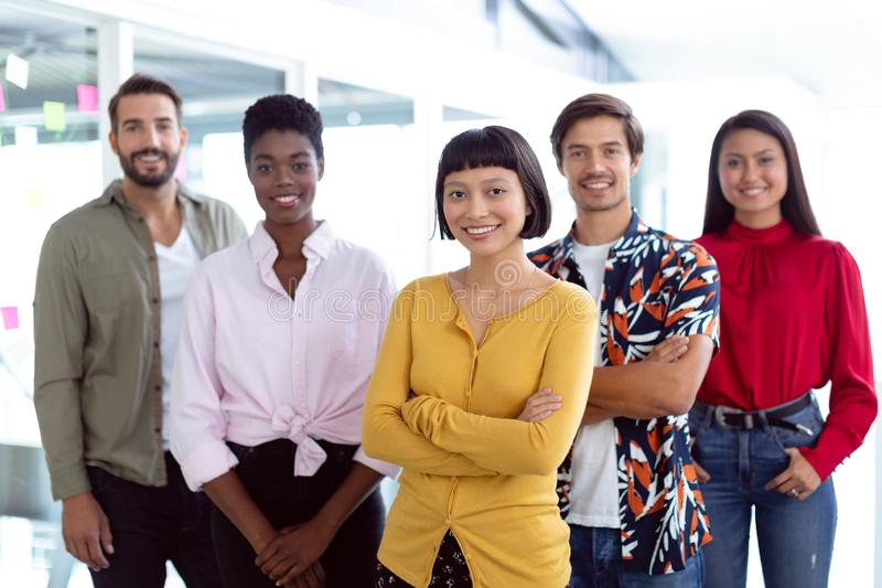 Business people looking at camera in a modern office. Front view of young diverse business people looking at camera in a modern office royalty free stock photography
