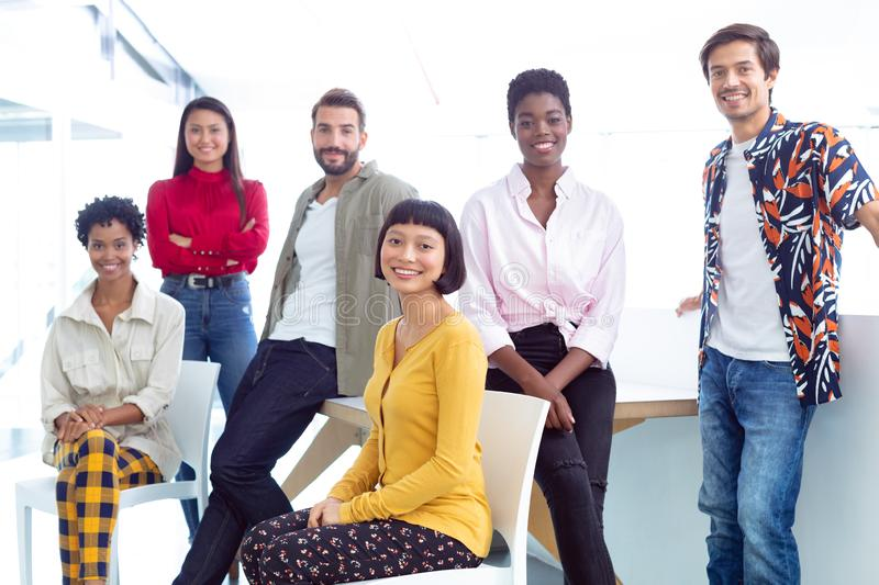 Business people looking at camera in a modern office. Front view of young diverse business people looking at camera in a modern office stock images
