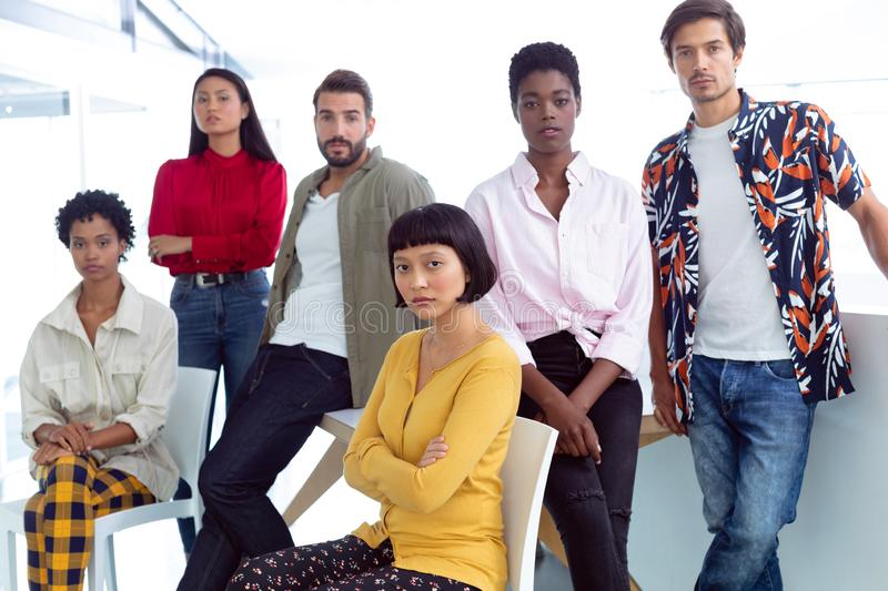 Business people looking at camera in a modern office. Front view of young diverse business people looking at camera in a modern office royalty free stock images