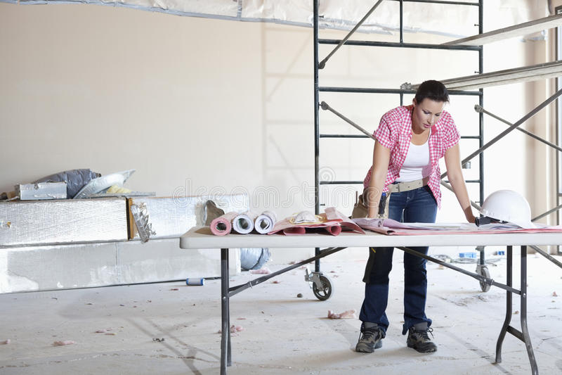 Front view of young female contractor looking at building plans at table stock photography