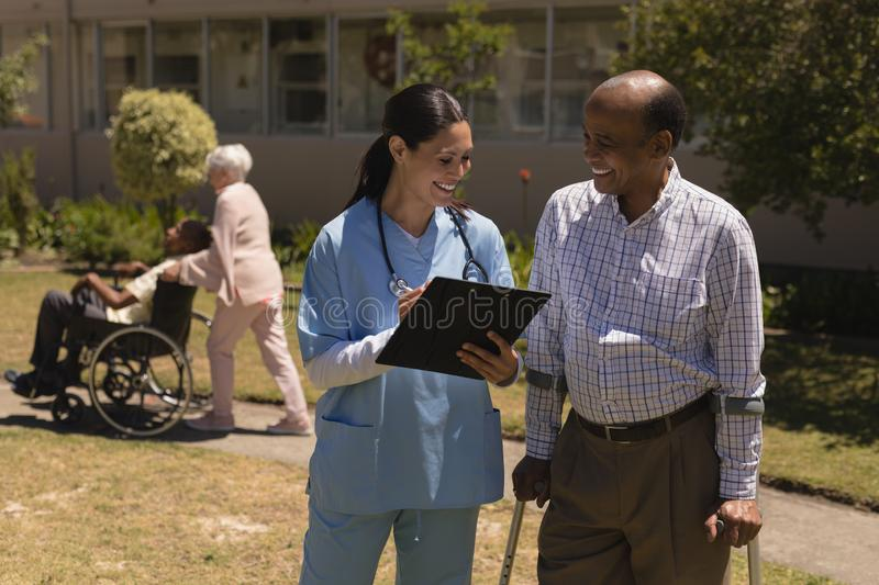 Front view of young female doctor discussing medical report with senior man on clipboard royalty free stock photos
