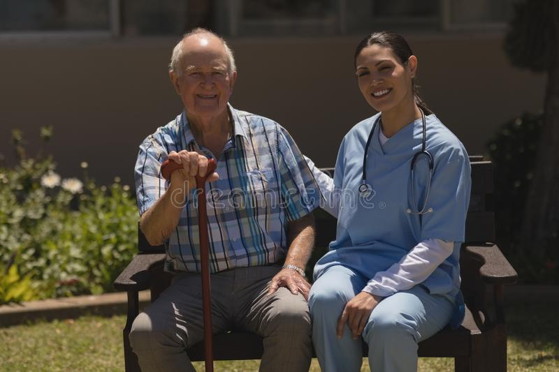 Front view of young female doctor and senior man looking at camera while sitting on bench royalty free stock photo