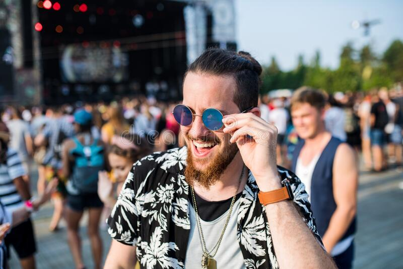 Front view of young man with sunglasses at summer festival. royalty free stock image