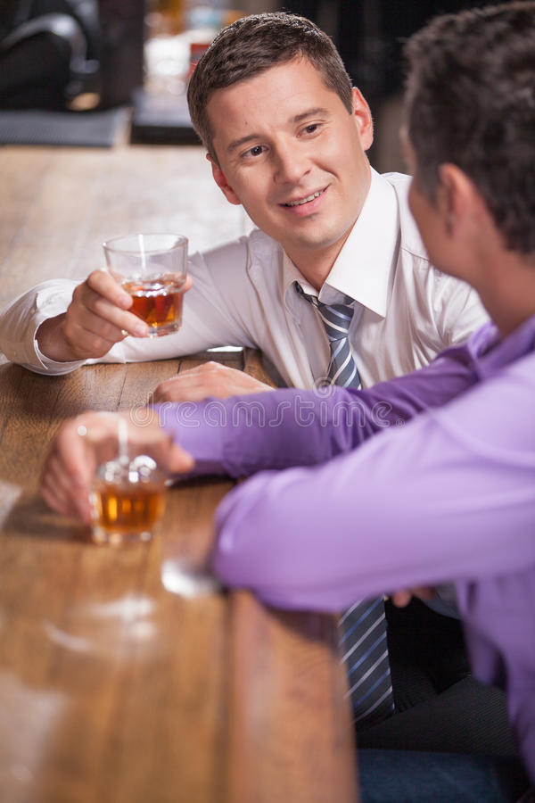 Front view of young man talking at counter. stock images