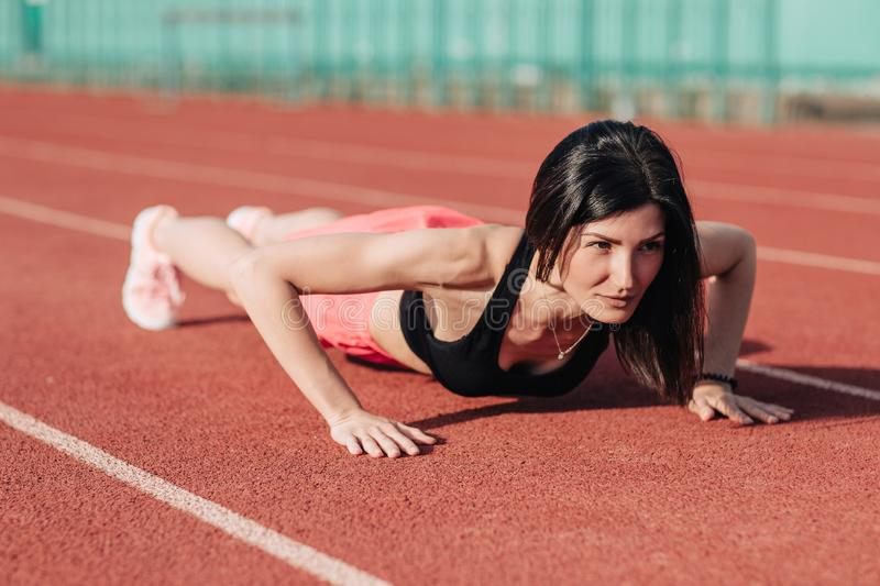 Front view of young slim attractive brunette woman in pink shorts and black top doing plank exercise at outdoor stadium, core. Front view of young slim stock photography