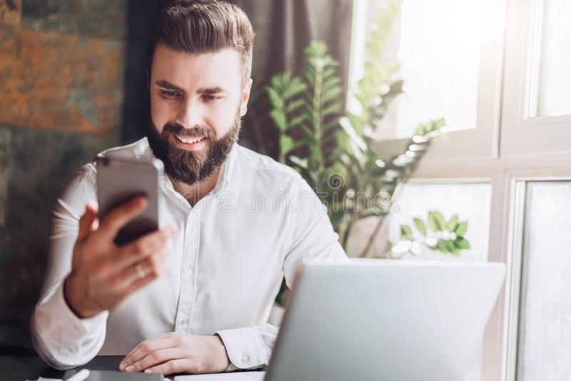 Front view. Young smiling bearded businessman is sitting in office at table in front of computer, using smartphone. stock images