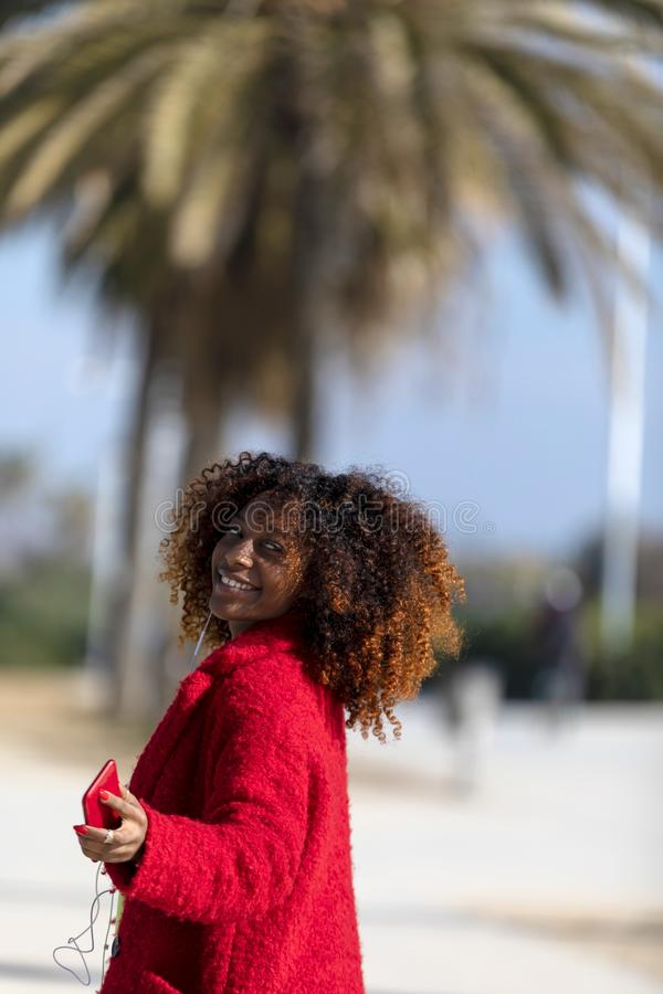 Front view of young smiling curly afro woman standing outdoors while smiling and looking away in a sunny day stock image