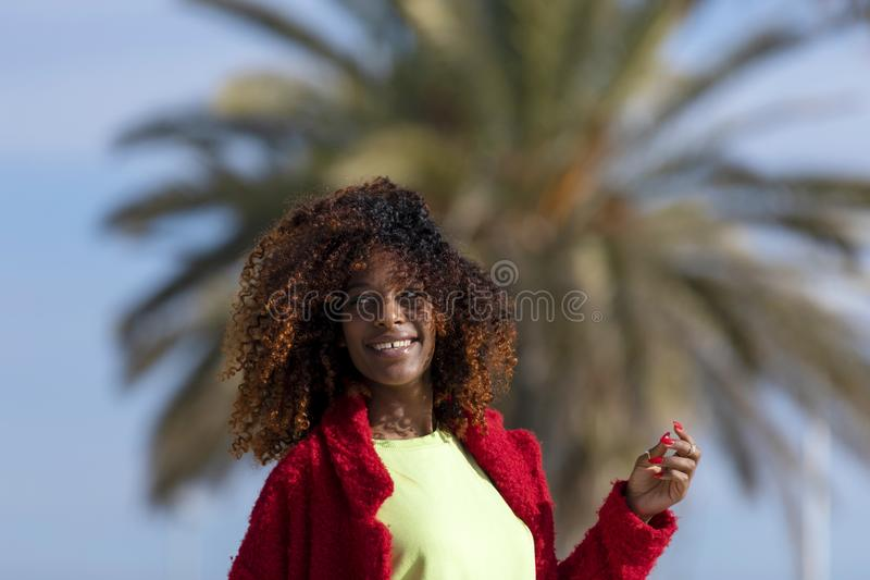 Front view of young smiling curly afro woman standing outdoors while smiling and looking away in a sunny day royalty free stock photo